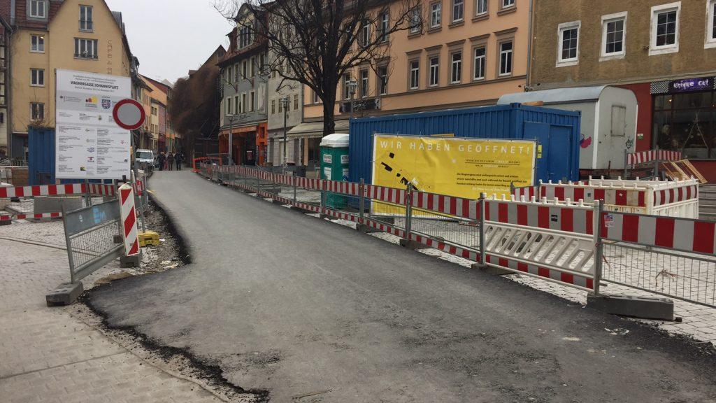 Die Wagnergasse und der Johannisplatz mit Baustelle, das Pflaster ist mit Asphalt bedeckt, links und rechts stehen Bauzäune.