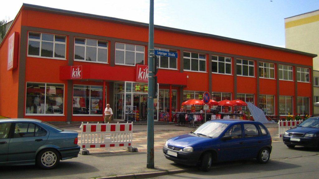 """Im Hintergrund das rote Gebäude des """"kik"""" am Emil-Höllein-Platz 1. Im Vordergrund der Platz, Gehweg und ein Stück der Straße."""