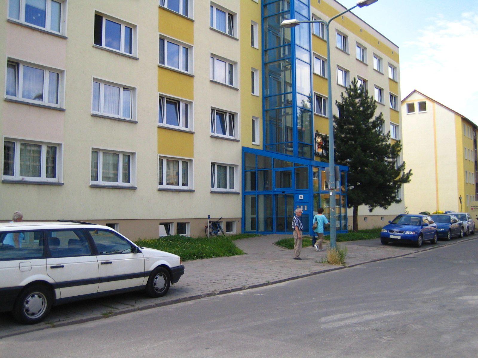 Blick in die Leipziger Straße. Auf dem Gehweg parken Autos, im Hintergrund Hausnummer 72.