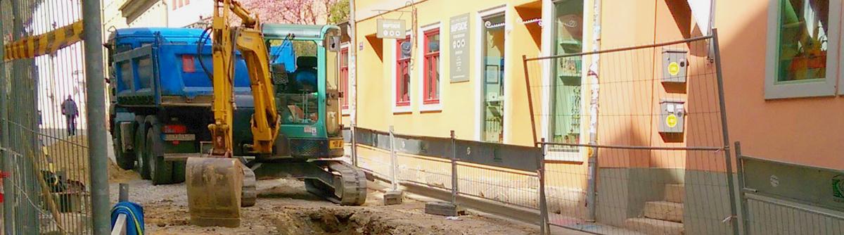 Bild zeigt einen gelben Bagger in einer Baustelle. Davor ein blauer Laster.