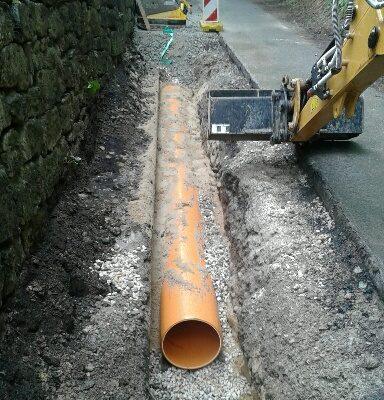 Baumaßnahme Bachverrohrung Ziegenhainer Straße. Hier eine Aufgrabung in der Straße mit Plane ausgelegt und ein teilweise zugeschüttetes Rohr.