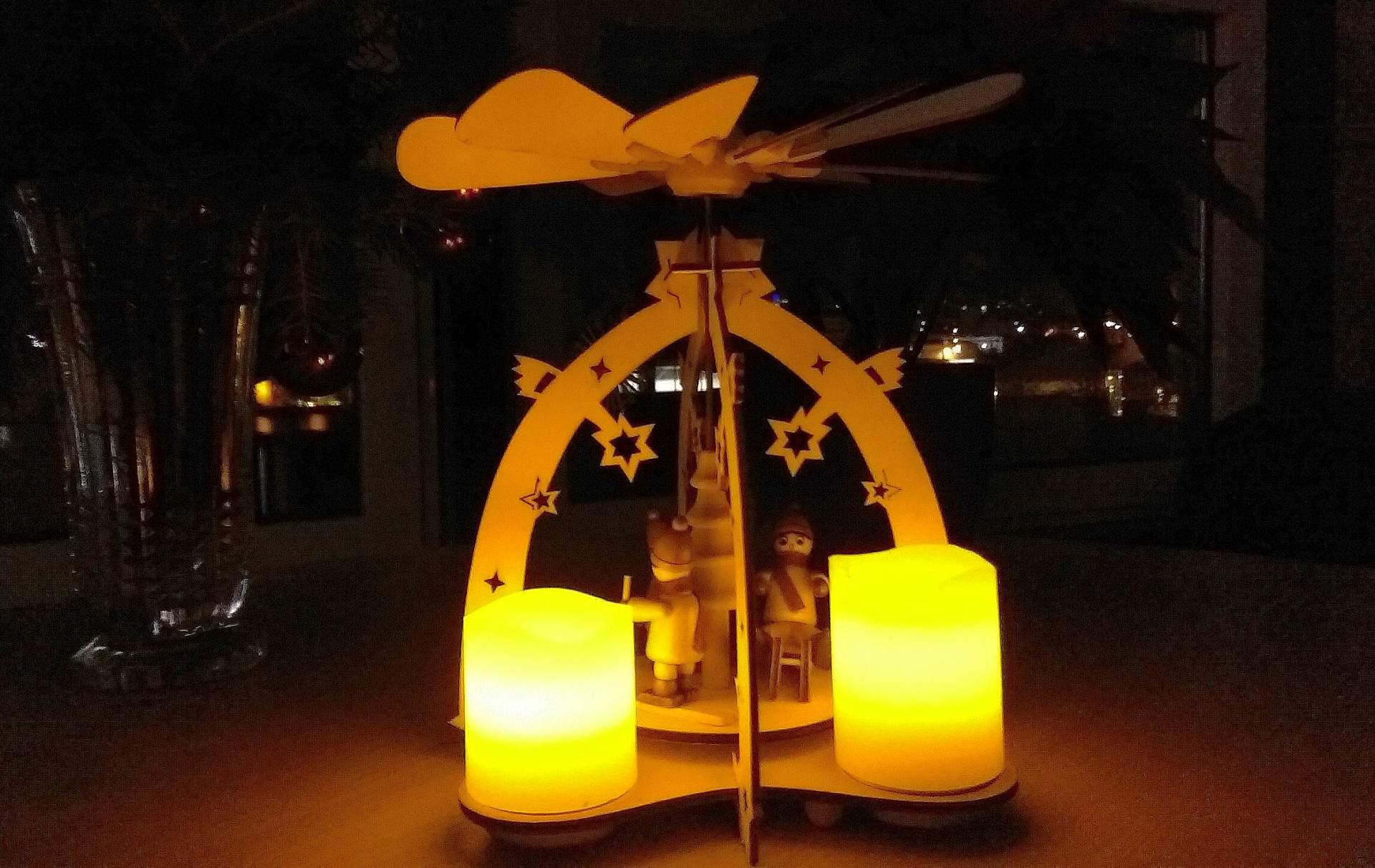 Eine kleine Holzpyramide mit Kerzen und Figuren