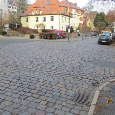 Blick in die Thomas-Mann-Straße, Kreuzung. Die Straße ist geplastert, rechts parken Autos.