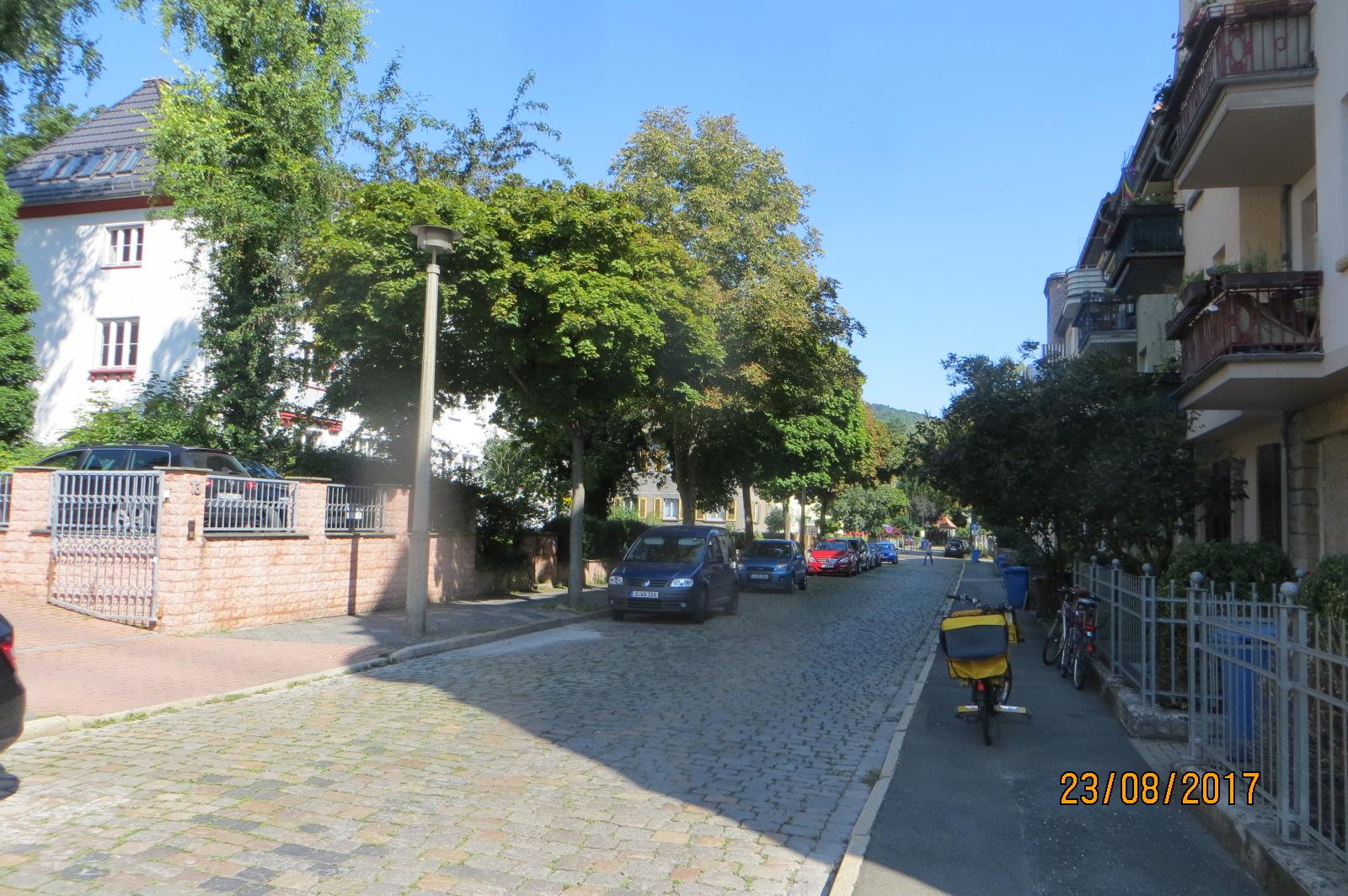 Blick in die Thomas-Mann-Straße, im Vordergrund auf dem Gehweg ein Post-Fahrrad.