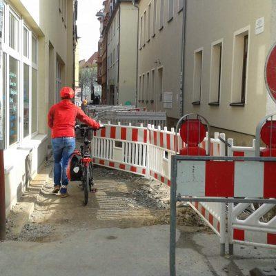 Blick in die Zwätzengasse, rechts die Absperrung, links der Gehbereich, eine Fußgängerin schiebt ein Fahrrad