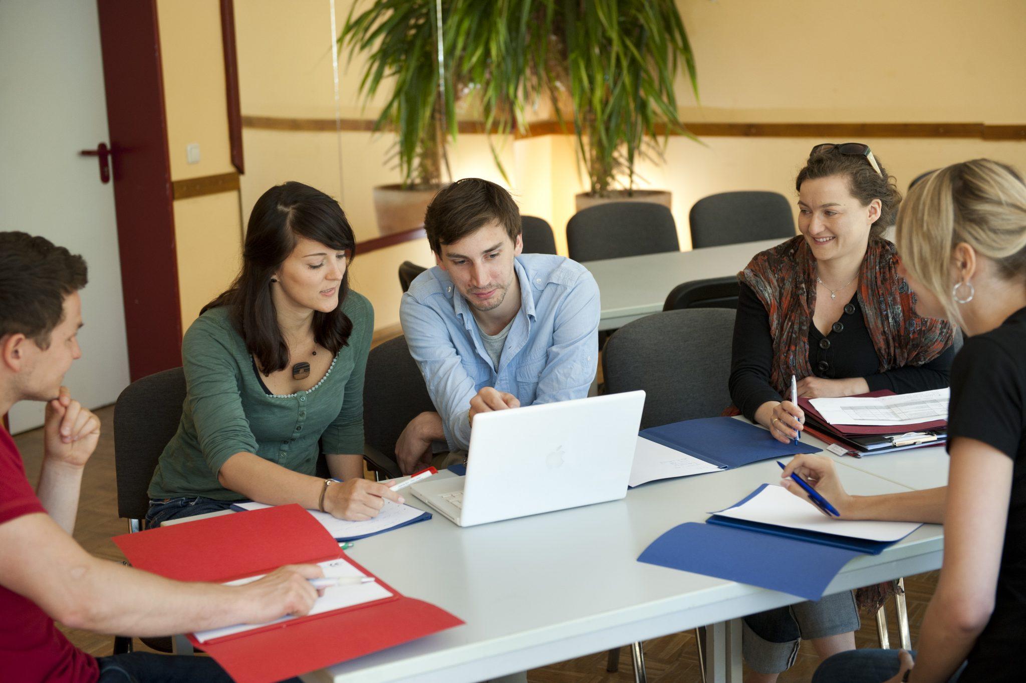 5 Personen diskutieren an einem Tisch. In der Mitte steht ein Laptop.