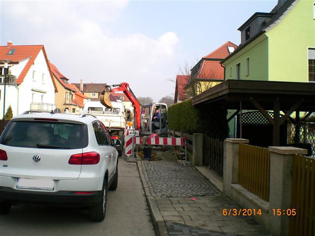 Blick in die Hienrich-Heine-Straße, im Vordergrund ein Auto im Hintergrund ist ein Klienbagger zu sehen, Links und rechts befinden sich Häuser.