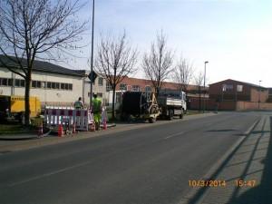 Eine Straße auf dem Bürgersteig steht ein LKW mit einer Kabeltrommel.