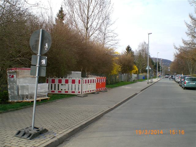 Blick in eine Straße. Am linken Rand ist eine Absperrung zu sehen und ein neuer Verteilerkasten.