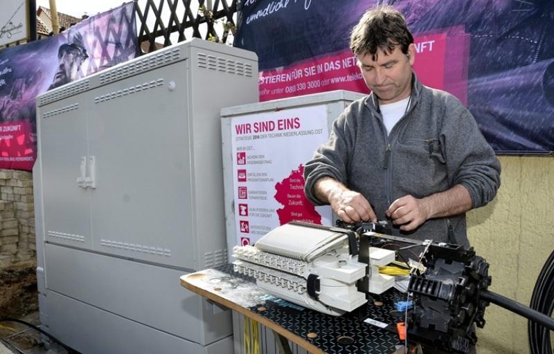 Techniker Frank Speerschneider von der Telekom cerknüpft hauchdünne Glasfaserkabel in einer Glasfasermuffe. Dahinter die neuen, größeren Verteilerkästen.