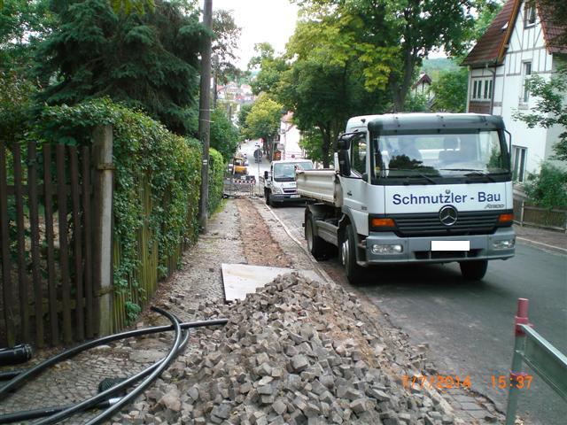 Blick in die Ebertstraße, es liegt ein Haufen mit Pflastersteinen im Vordergrund. Die Spuren des aufgegrabenen Gehwegs sind noch sichtbar.