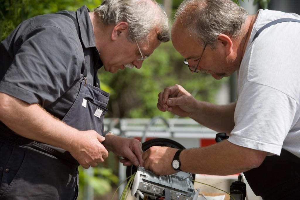 Zwei Männer bauen gebeugt über einen Glasfaserverzweiger
