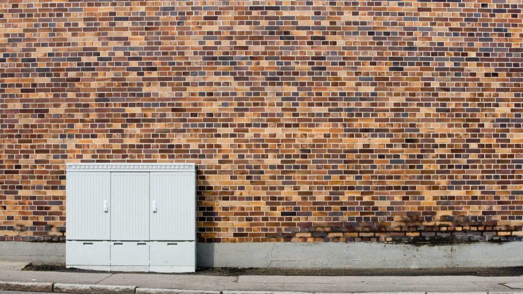 Ein Verteilerkasten steht vor eine Hauswand aus Backsteinen © Deutsche Telekom