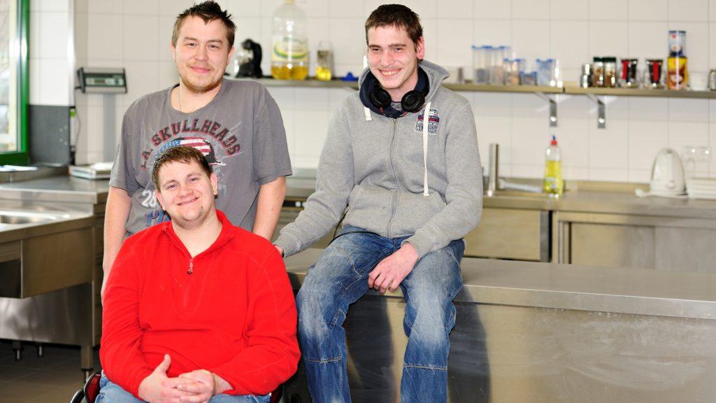 In einer Werkstatt sitzt eine Person in einem Rollstuhl, dahinter 2 Personen auf einer Werkbank.