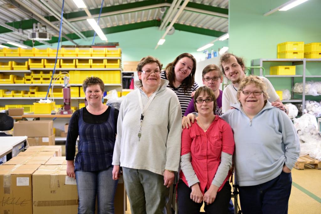 Mehrere Personen stehen zusammen in einer Werkstatt