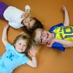 3 Kinder liegen mit dem Rücken auf dem Boden und winken mit ihren Armen