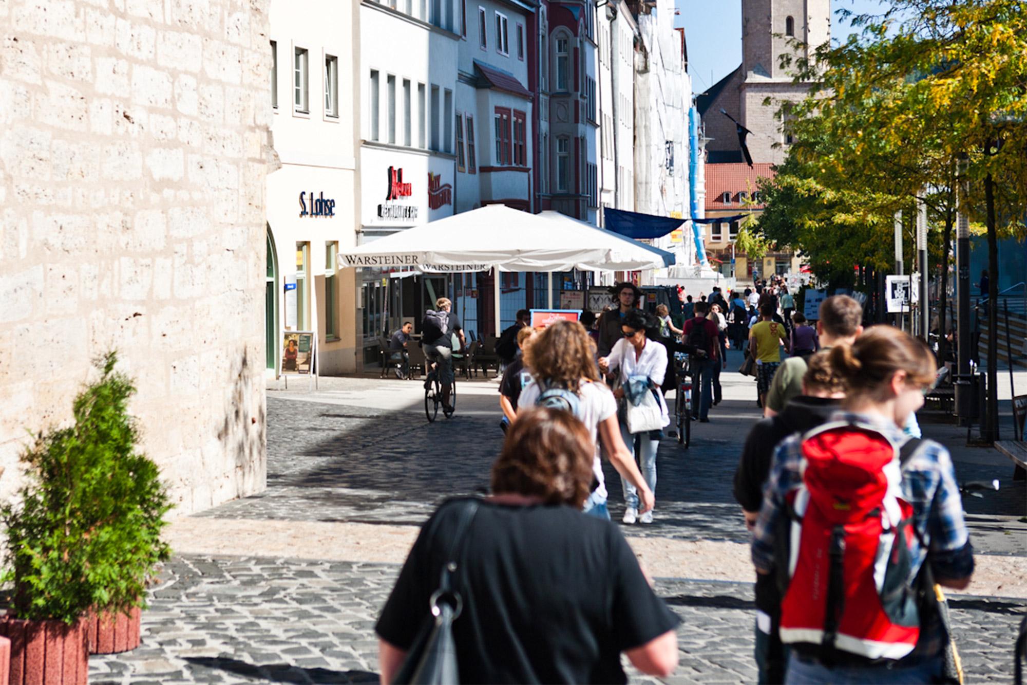 Menschen laufen durch eine Fußgängerzone in der Innenstadt von Jena