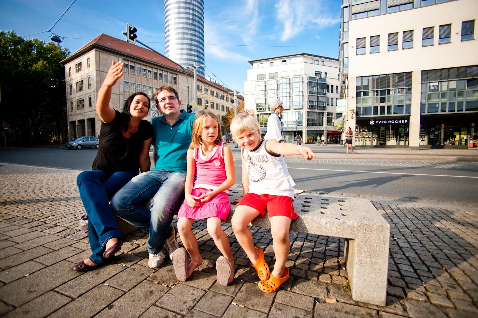 Freundliche Famile winkt, im Hintergrund ist der Intershoptower in Jena zu sehen.