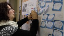 Eine Bürgerin schreibt einen Vorschlag auf und klebt ihn zur Weiterbearbeitung auf die vorbereiteten Poster