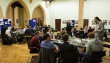 Personen sitzen an vier Tischen verteilt und disktutieren.