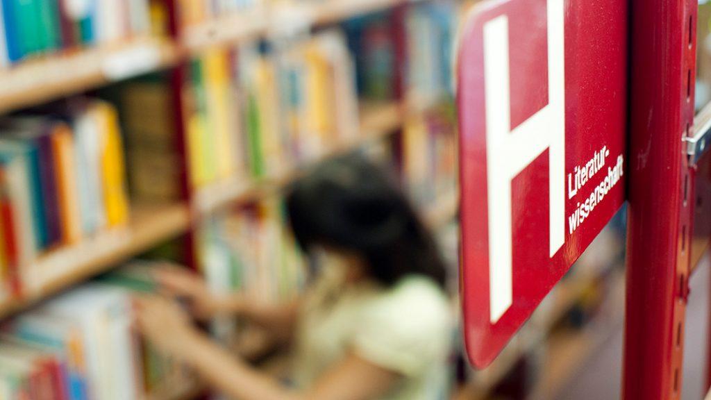 Eine Nutzerin stöbert in den Regalen der Ernst-Abbe-Bücherei Jena