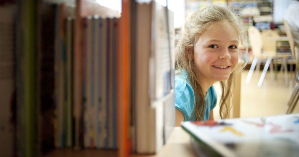 Kind hinter Bücherregalen