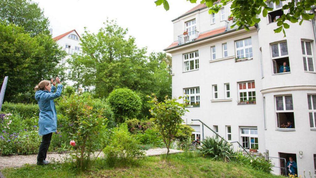 Eine Frau steht vor einem Wohnhaus in Jena und dirigiert die Bewohner, die aus dem Fenstern heraus ein Konzert geben