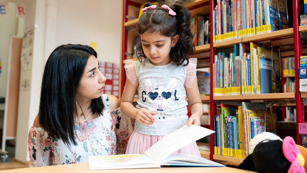 Eine junge dunkelhaarige Frau schaut sich gemeinsam mit einem kleinen, dunklehaarigen Mädchen ein Buch in einer Bücherei an