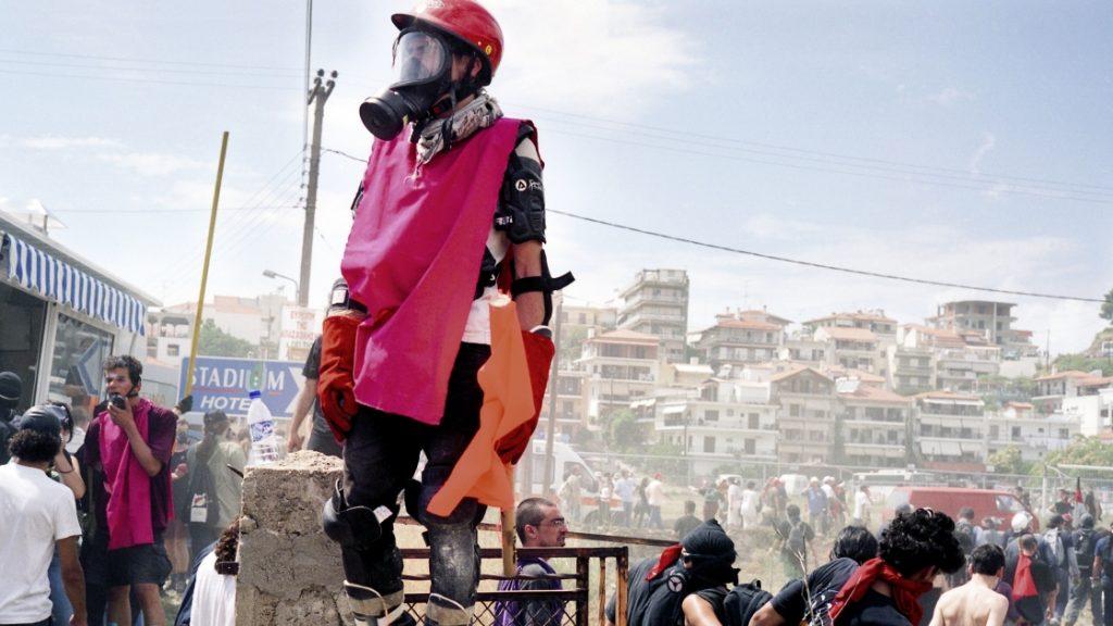Fotografie von Julian Röder: Mit Gasmaske und Schutzbekleidung ausgestatteter Mann auf einer Barrikade mit Menschen und Häusern im Hintergrund