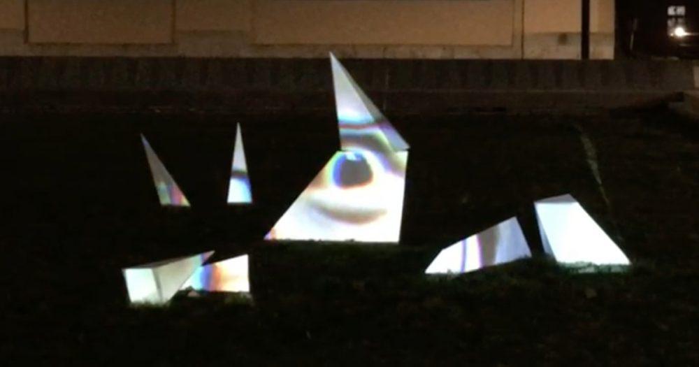 Fotografie einer zersplitterten Pyramidenform, auf die ein stark vergrößertes Gesicht projiziert wurde
