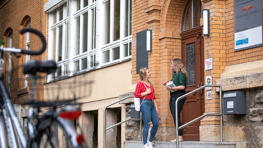 Eingang der Ernst-Abbe-Bücherei Jena 2021 mit 2 jungen Damen