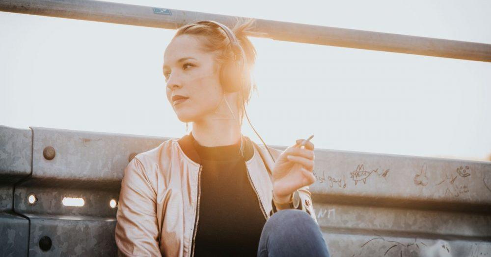 DJane Janine Herold mit Kopfhörern lehnt an einer Leitplanke und raucht