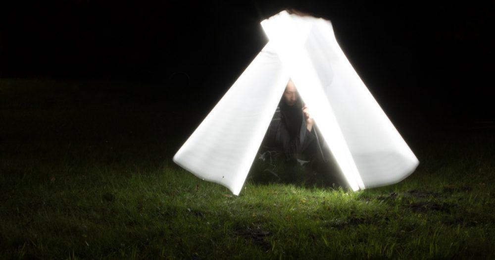 Fotografie einer Person mit Leuchtstoffröhre, die mit dem Licht ein Zelt um sich herum nachbildet