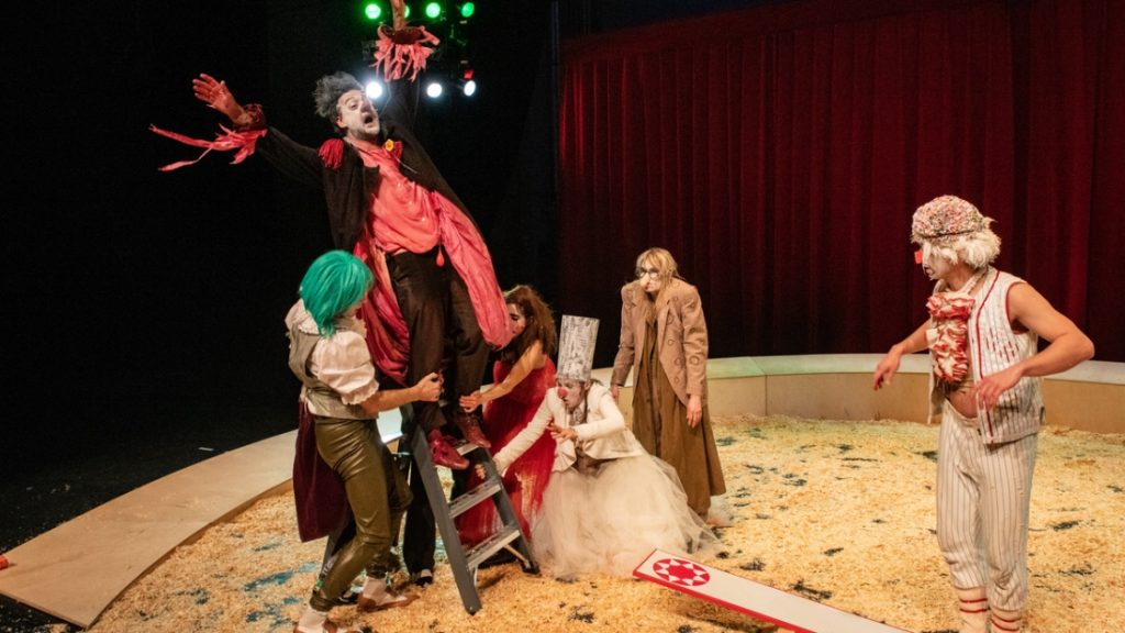 """Szene aus der Vorstellung """"Der Clowns-Kongress"""": Ein Clown schwankt auf einer Leiter, andere halten ihn fest. Ein weiterer Clown auf einer Wippe daneben"""