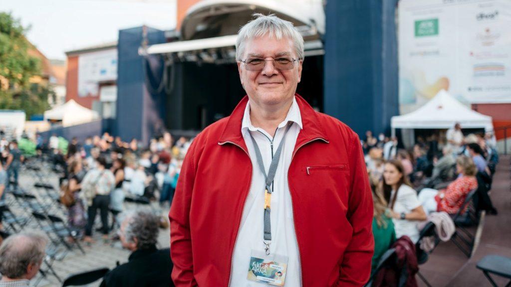 Lutz Engelhardt mit einem Ausweis der Kulturarena 2021 auf dem Theatervorplatz