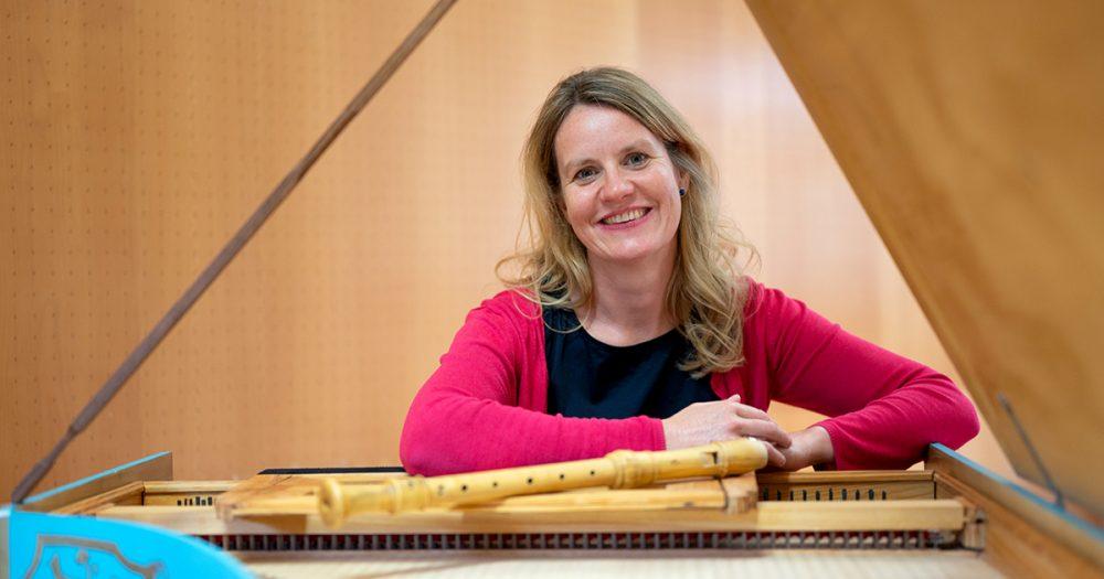 Yvonne Krüger mit Flöte auf einem Cello lehnend