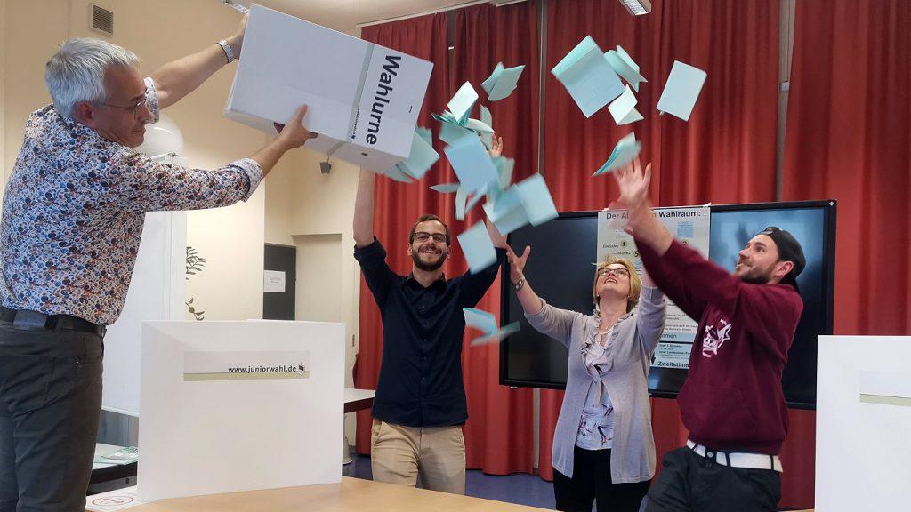 Das Team der vhs freut sich über die zahlreichen Stimmzettel bei der Juniorwahl 2021, vier Mitarbeiter:innen leeren die Wahlurne mit viel Vorfreude