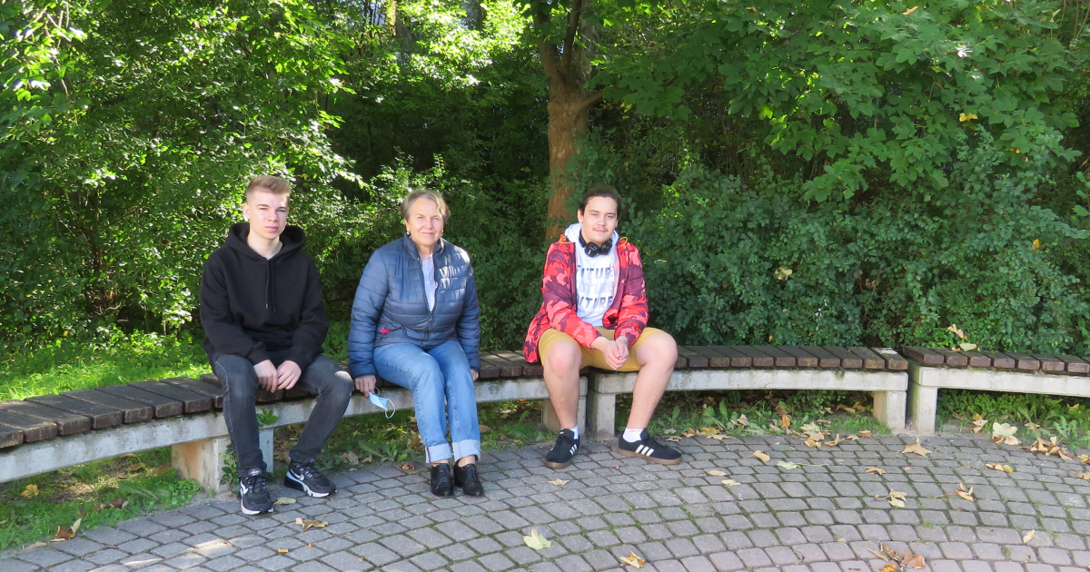 Jovan Schwabe, Monika Klaus und Jonas Hielscher sitzen auf einer Bank im Außengelände des LISA Lobeda