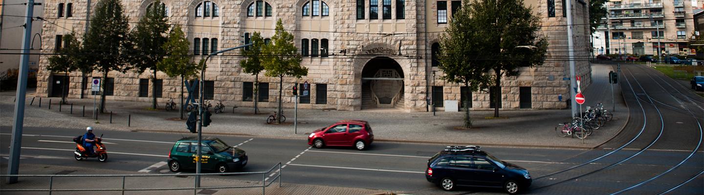Autos fahren auf einer Straße vor dem Volksbad in Jena.