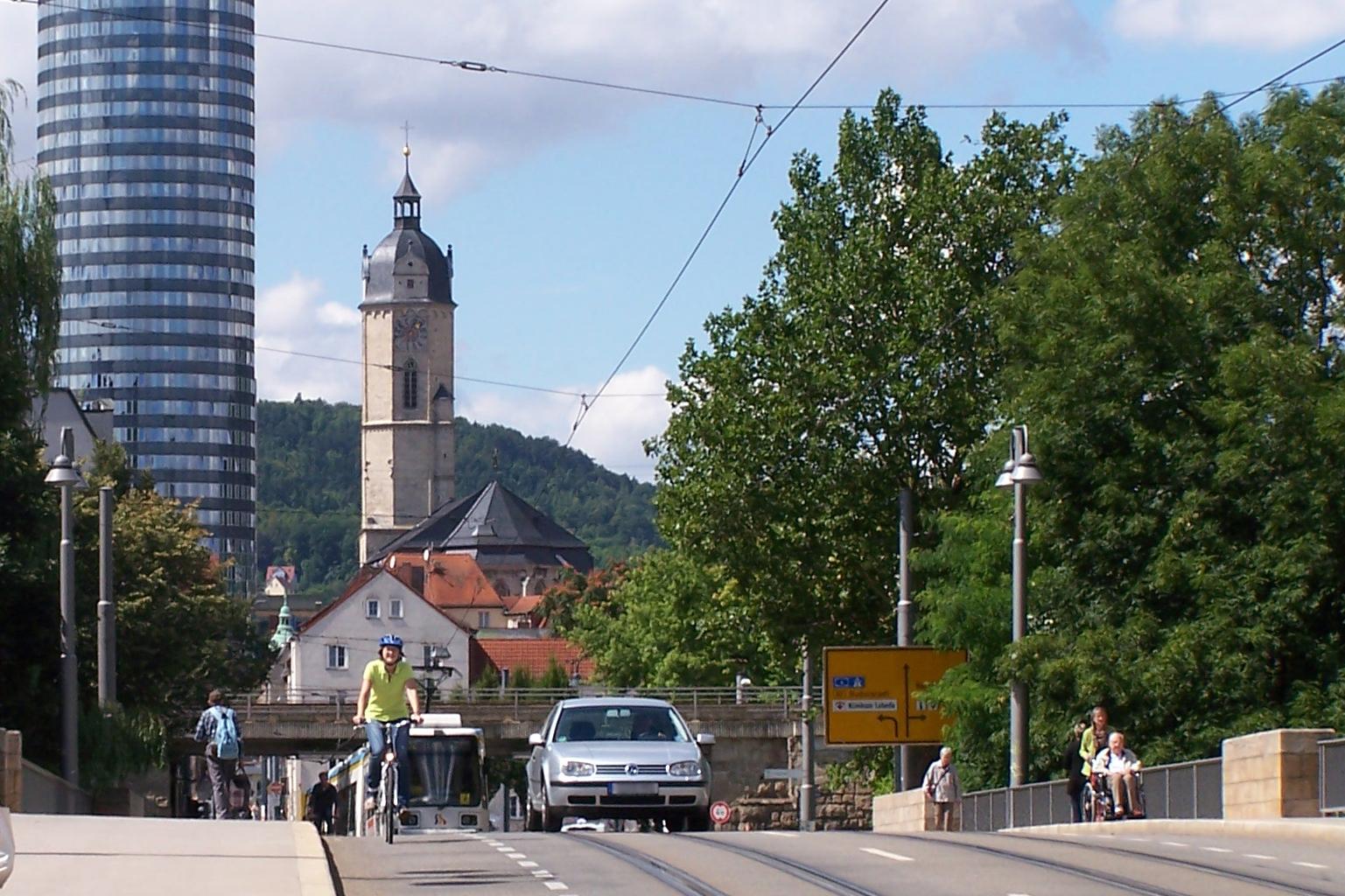 Auto und Fahrradfahrer fahren über eine Brücke in Jena.