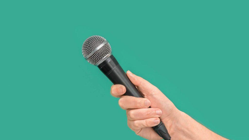 Hand hält Mikrofon vor grüner Wand.