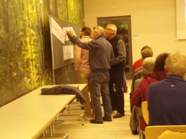 Interessierte schauen sich Karten an einer Tafel bei der Bürgerversammlung am 04.11.2014 an. © Stadt Jena