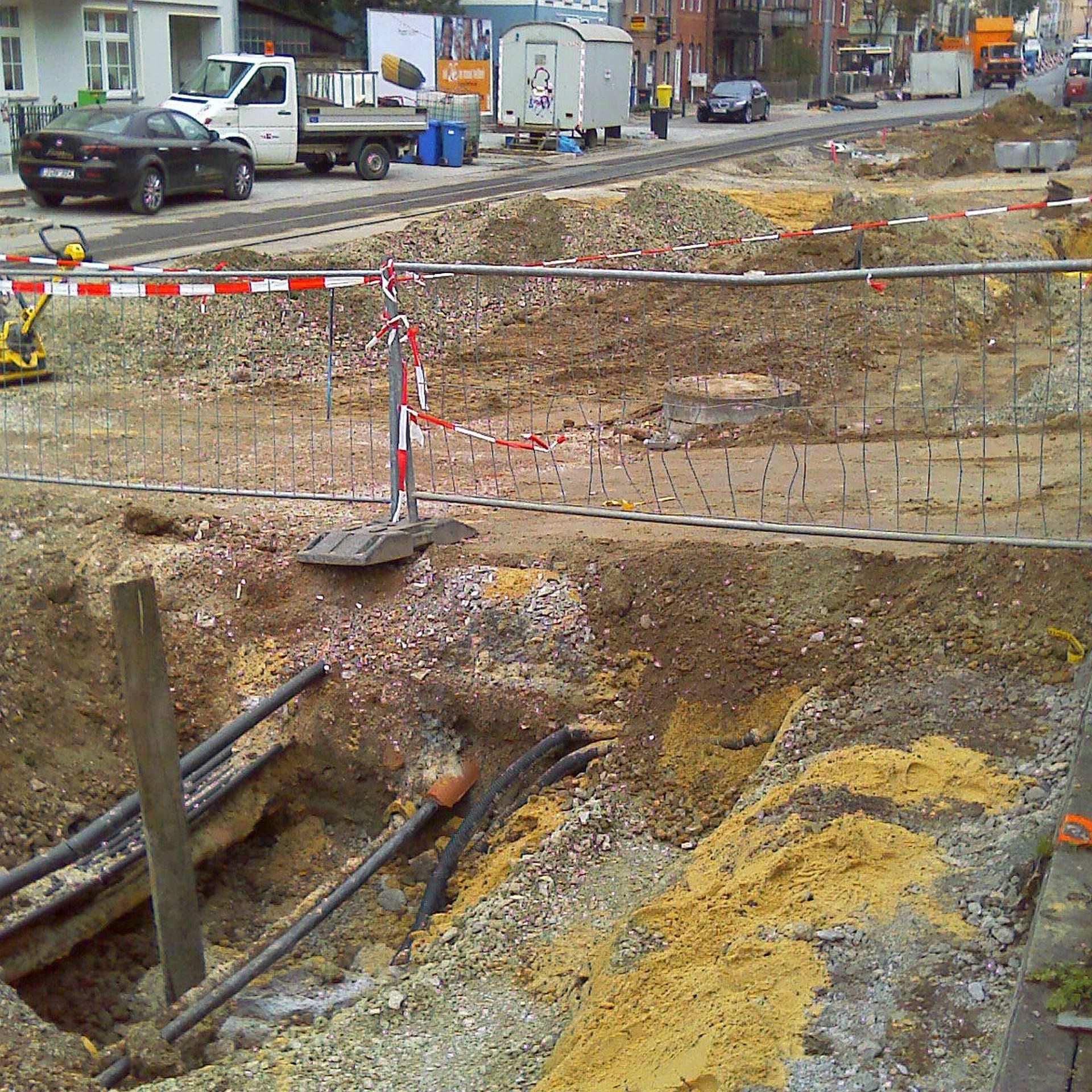 Tiefbauarbeiten / Straßenbau in Jena. Man sieht eine aufgerissene Straße mit verschiedenen Erdstoffen udn Schotter. Darin befindet sich eine Versorgungsleitung. Die Baustelle ist mit Gittern und Flatterband abgesichert.- Symbolfoto © KSJ