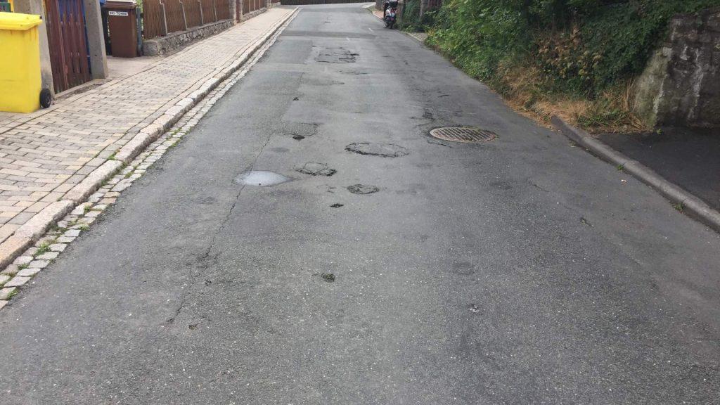 Blick in die Netzstraße vor dem Ausbau. Links der Gehweg, daneben die asphaltierte Straße mit sichtbaren Schäden.