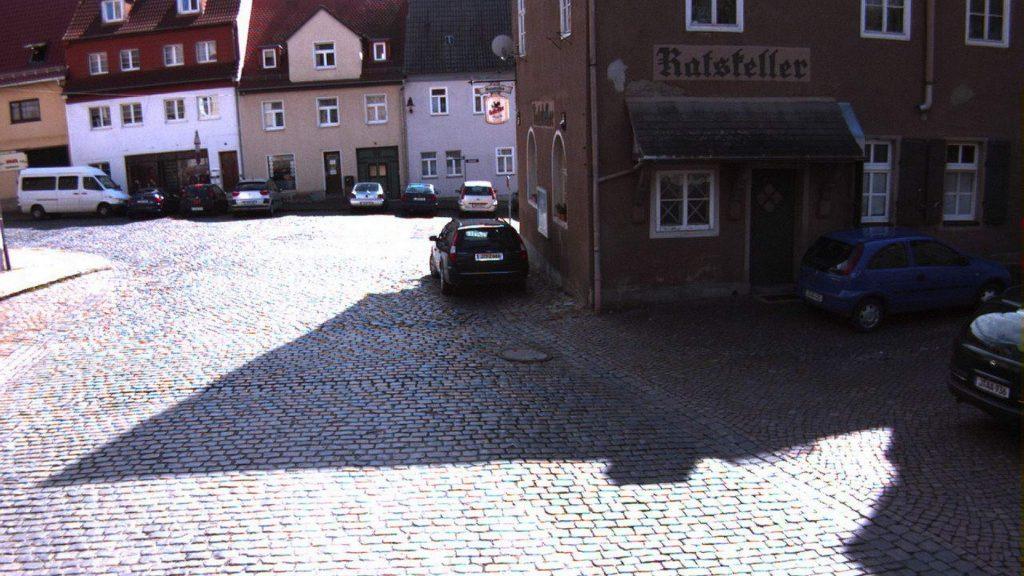 Der Stadthof in Jena Lobeda-Altstadt vor der Baumaßnahme, die Straße ist mit Kopfsteinpflaster ausgelegt. Im Vordergrund ein parkendes Auto.