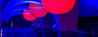 Ein Gewölbe blau angestrahlt an der Decke leuchten große rote Laternen